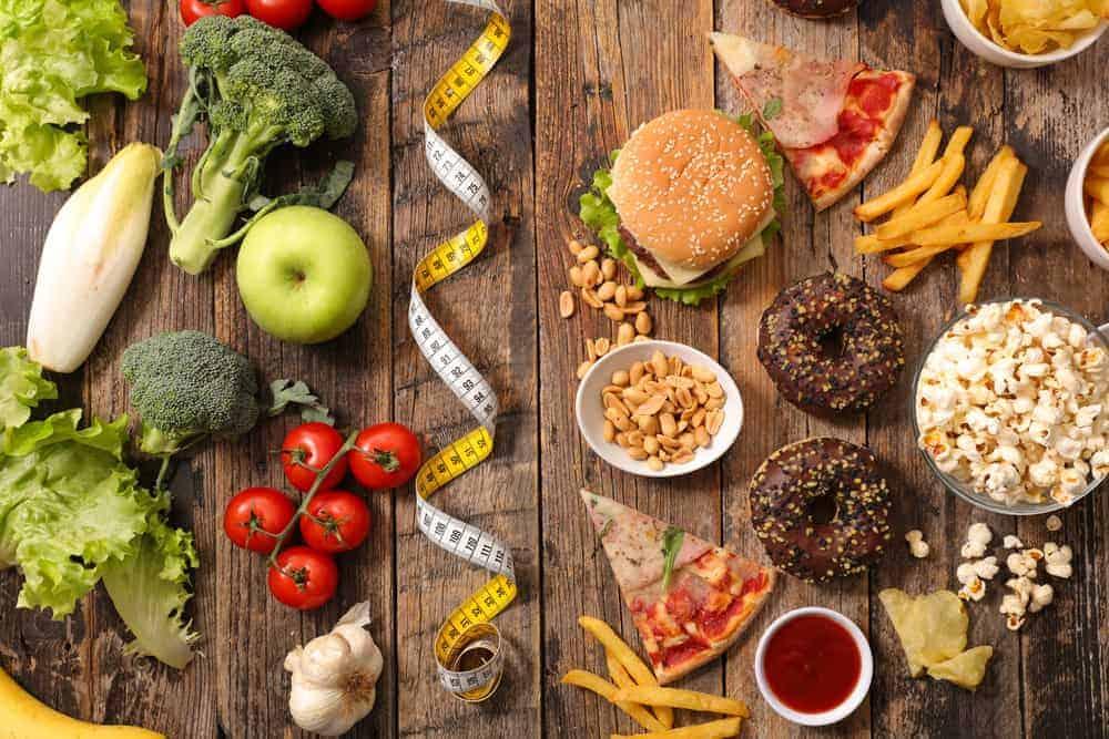 Gesundes Obst und Gemüse auf der linken Seite eines Holztischs durch Maßband von Junkfood auf der rechten Seite getrennt