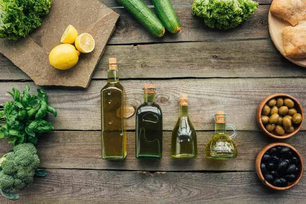 Vier verschiedene Öle in Flaschen auf Holztisch mit Kräutern, Zitronen und Oliven im Hintergrund