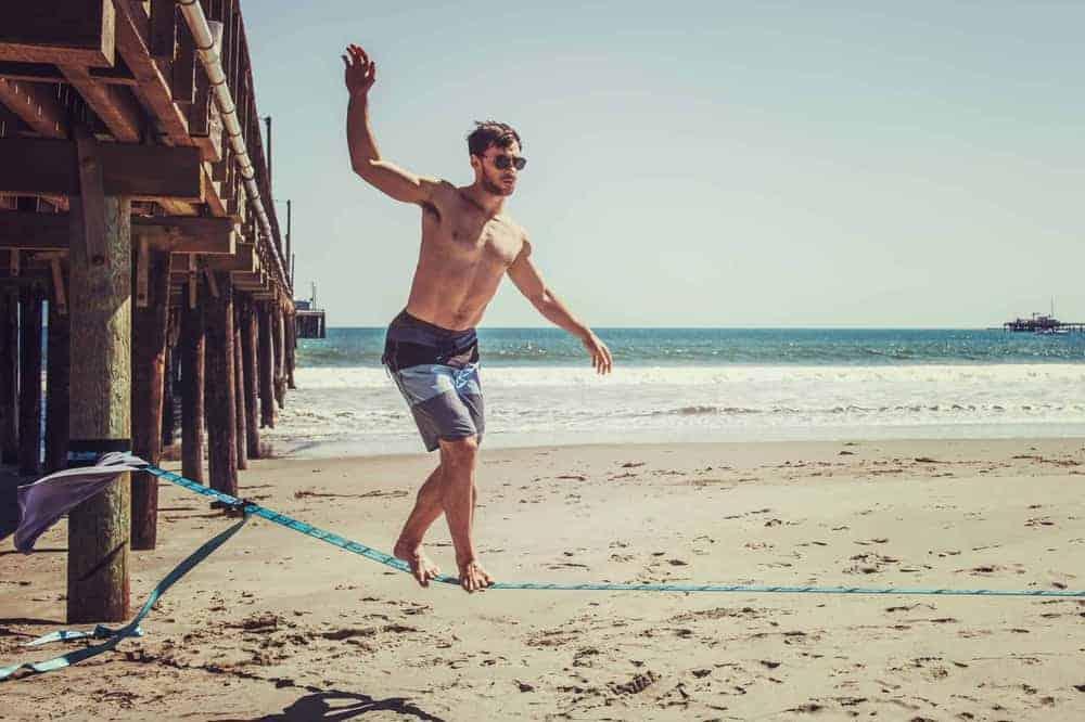 Junger Mann auf Slackline am Strand mit Meer im Hintergrund