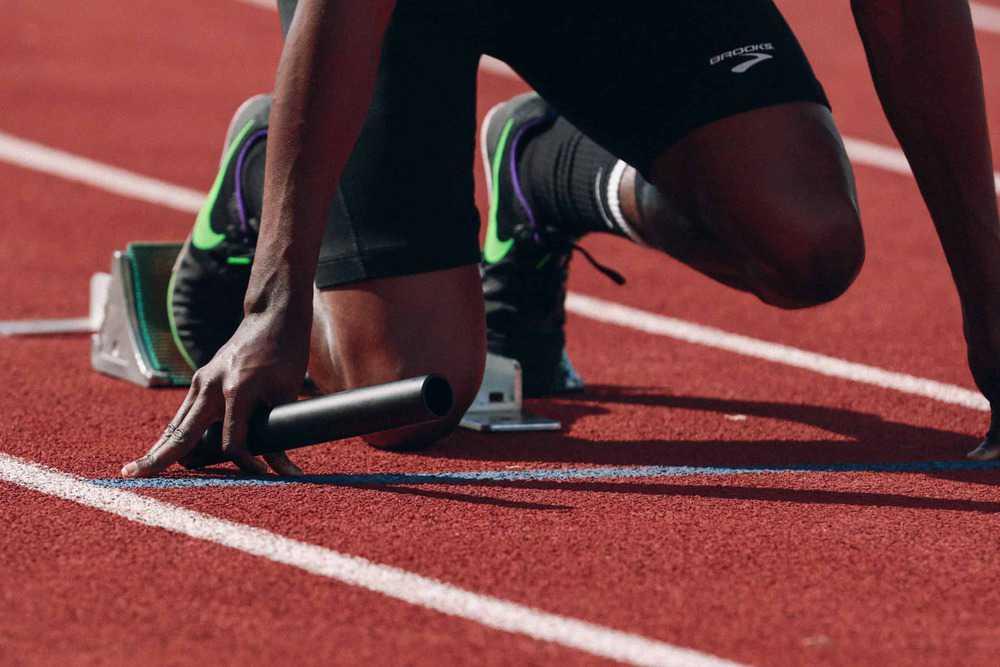 Junger Mann in Startposition beim Sprint auf Aschenbahn
