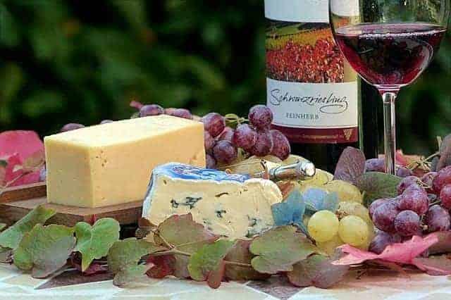 Gereifter Käse, Rotwein, Butter und Trauben auf Gartentisch