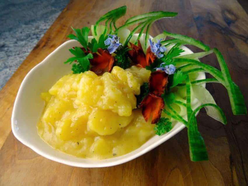 Kartoffelsalat hübsch garniert mit Karotte und Kräutern auf Holzbrett