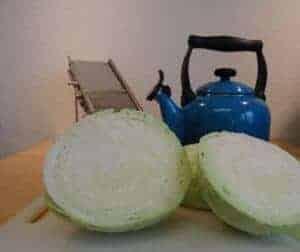 Weisskraut auf weissem Brett mit Hobel, Wasserkocher und Messer auf Holztisch