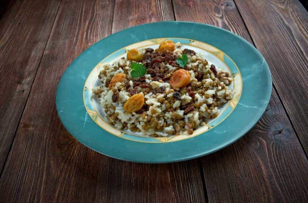 Reis-Linsen-Gemüse-Pfanne in türkisem Teller auf Holztisch