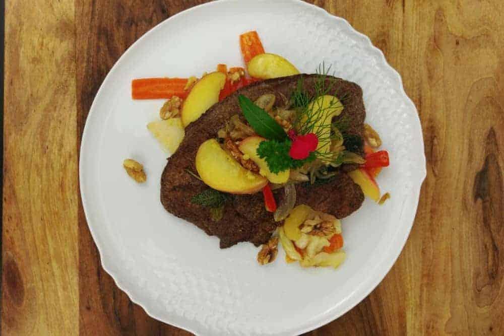 Weisser Teller auf Holz mit farbigem Gemüse und paniertem Fleisch