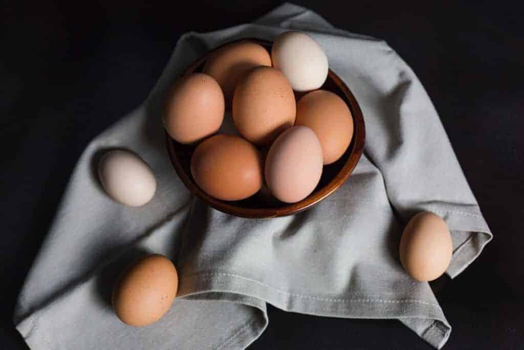 Braune und weiße Eier in Tonschale auf grauem Geschirrtuch