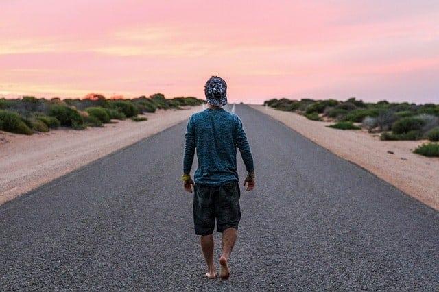 Junger Mann geht Sonnenaufgang auf Teerstraße entgegen